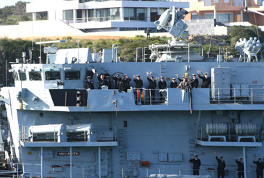 The officers and crew of HMS Monmouth wave goodbye as the ship departs.